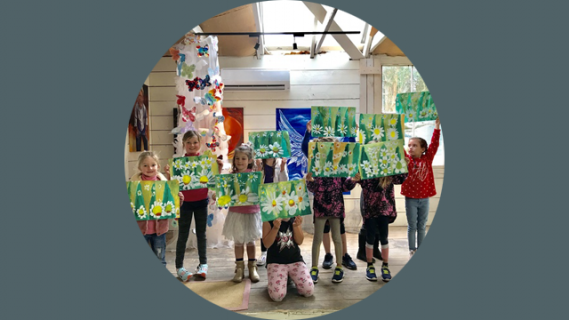Several children holding paintings
