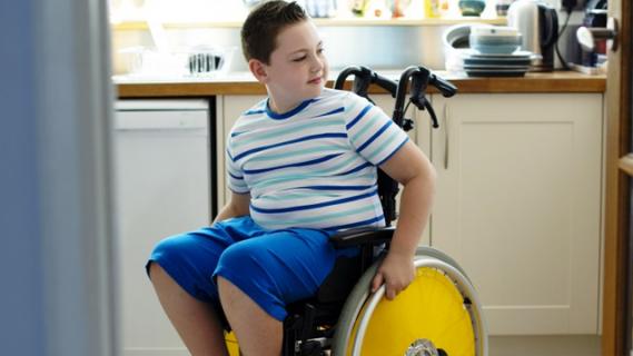 Boy in wheelchair next to kitchen bench