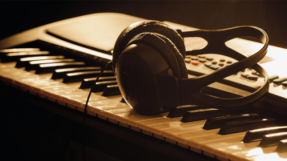 Photograph of a set of headphones on top of an electronic piano keyboard
